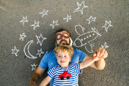 Portrait of mature man wearing pilot hat and his little son lying on asphalt painted with airplane, moon and stars - gettyimageskorea