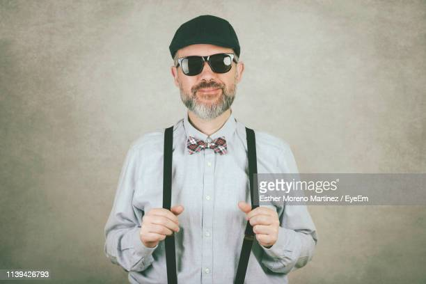 portrait of mature man wearing sunglasses while standing against wall - サスペンダー ストックフォトと画像
