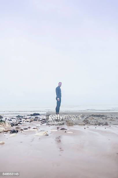 Portrait of mature man wearing wetsuit, standing on beach