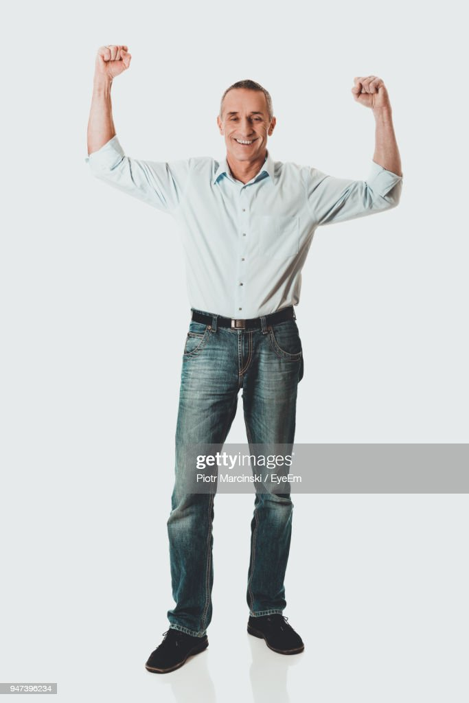 Portrait Of Mature Man With Arms Raised Standing Against White Background : Stock Photo