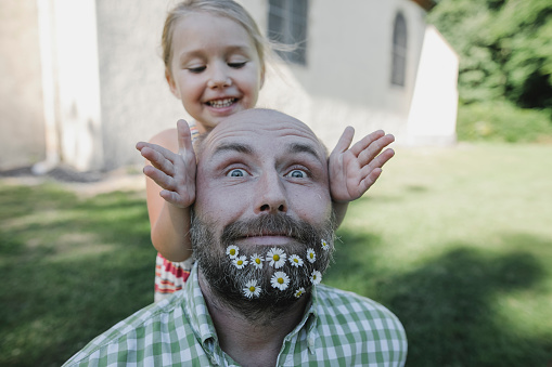 Portrait of mature man with daisies in his beard playing with little daughter in the garden - gettyimageskorea