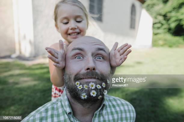 portrait of mature man with daisies in his beard playing with little daughter in the garden - barba peluria del viso foto e immagini stock