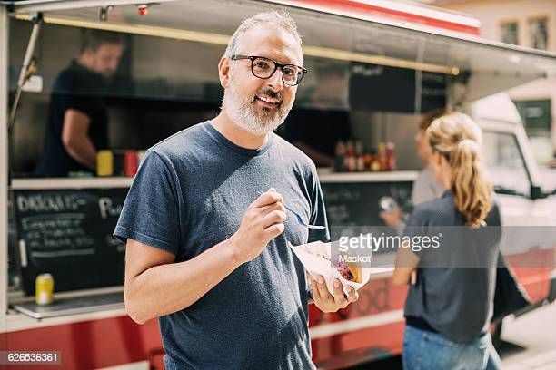 Portrait of mature man with food standing against truck at street