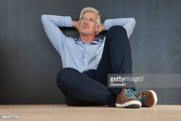 Portrait of mature man with hands behind his head sitting on the floor in front of a grey wall