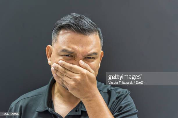 portrait of mature man with hands covering nose against black background - olor desagradable fotografías e imágenes de stock