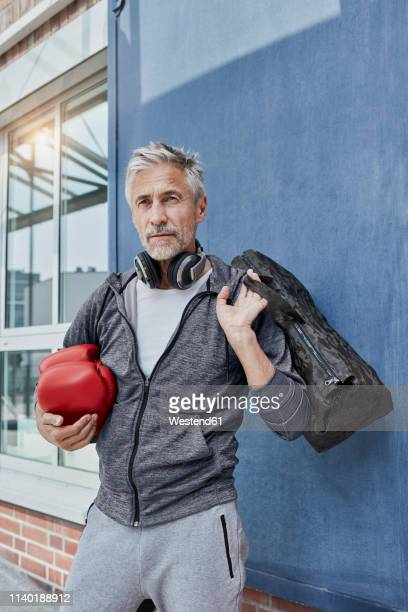 portrait of mature man with headphones, sports bag and red boxing gloves standing in front of gym - 55 59 años fotografías e imágenes de stock