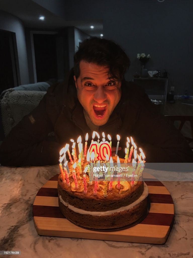 Portrait Of Mature Man With Mouth Open By Birthday Cake On Table : Stock Photo