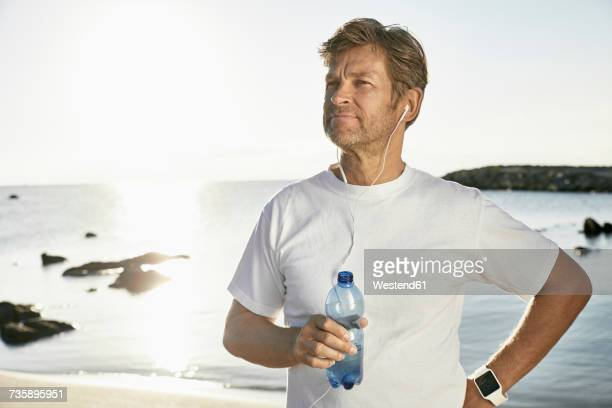 Portrait of mature man with smartwatch and earphones drinking water after jogging on the beach