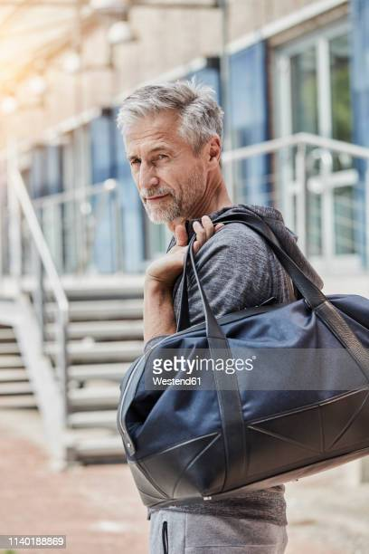 portrait of mature man with sports bag standing in front of gym - gym bag stock pictures, royalty-free photos & images