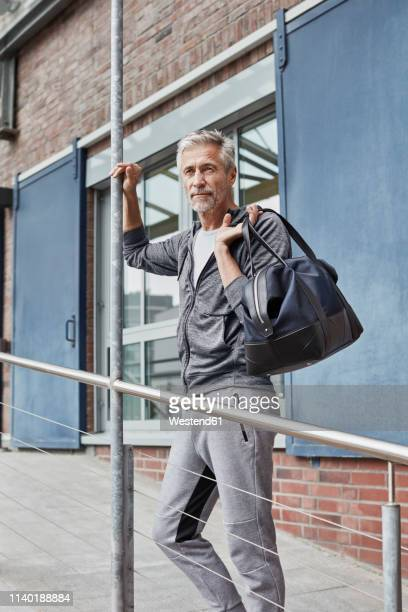 portrait of mature man with sports bag standing in front of gym - 55 59 años fotografías e imágenes de stock