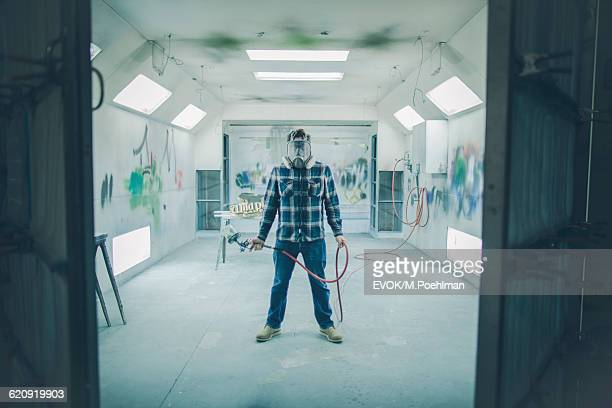 Portrait of Mature Man with Spray gun in industrial spray paint room