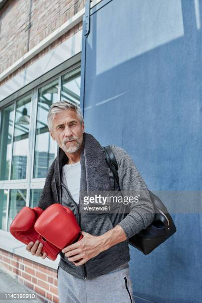 portrait of mature man with towel, sports bag and red boxing gloves standing in front of gym - trainingsanzug stock-fotos und bilder