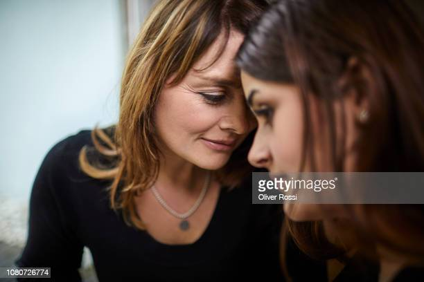 portrait of mature mother with teenage daughter close together - consoling stock pictures, royalty-free photos & images