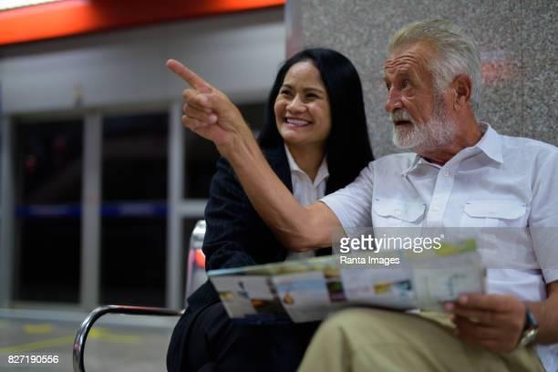 Portrait of mature multi-ethnic couple inside MRT subway train station in Bangkok Thailand