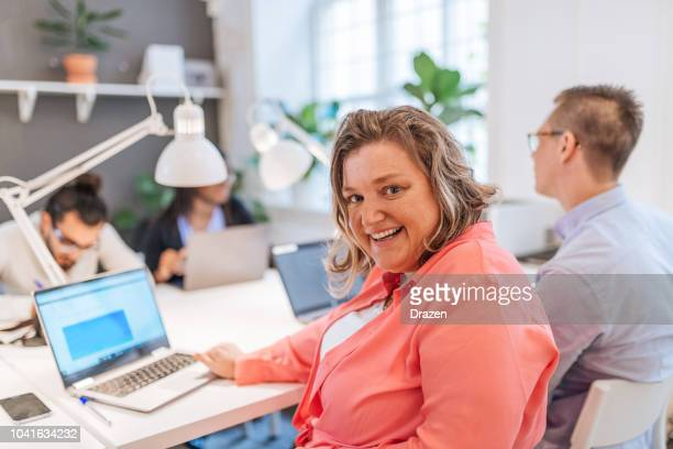 portrait of mature scandinavian businesswoman in open plan office - arab women fat stock pictures, royalty-free photos & images