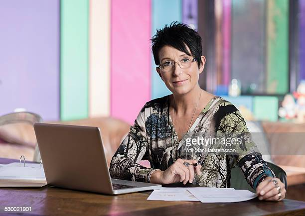 Portrait of mature seamstress using laptop in workshop office
