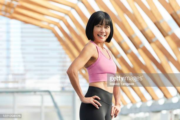 portrait of mature sportswoman - arms akimbo stock pictures, royalty-free photos & images