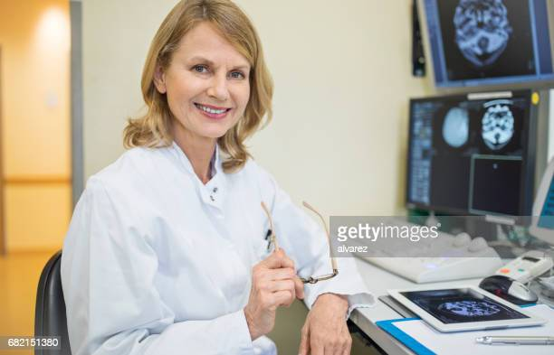 Portrait of mature surgeon with CT scan reports