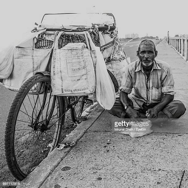 Portrait Of Mature Vendor Sitting On Footpath By Bicycle Against Sky