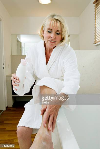 portrait of mature woman applying body lotion