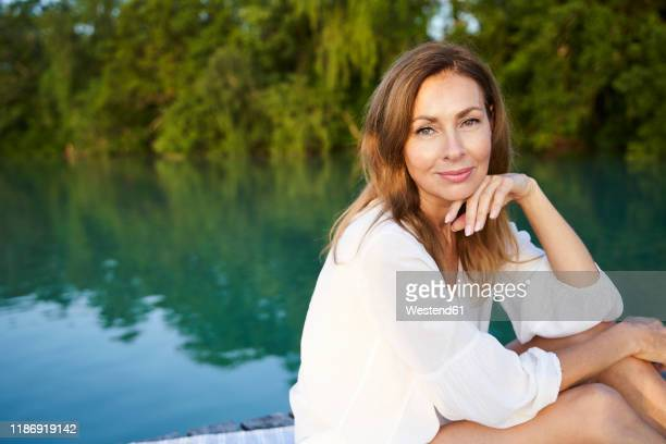 portrait of mature woman at a lake - kin in de hand stockfoto's en -beelden
