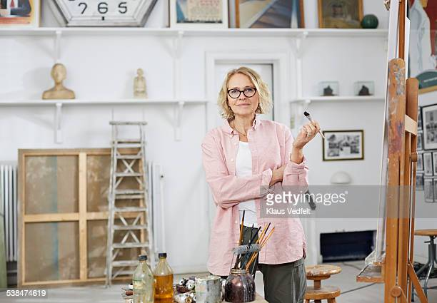 portrait of mature woman at her home studio - blonde glasses stock-fotos und bilder
