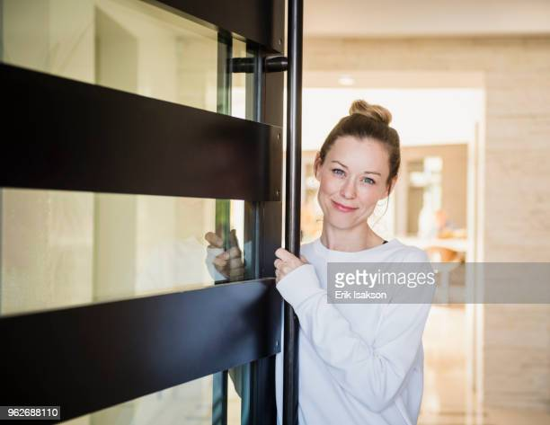 portrait of mature woman at home - doorway stock pictures, royalty-free photos & images