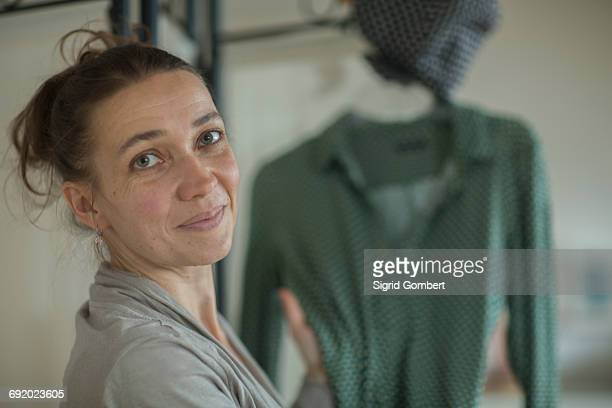 portrait of mature woman choosing what to wear - sigrid gombert stock pictures, royalty-free photos & images