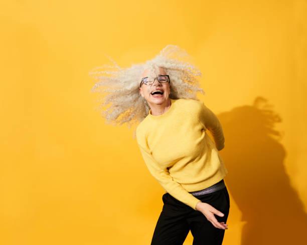 portrait of mature woman dancing, smiling and having fun - 彩色影像 個照片及圖片檔