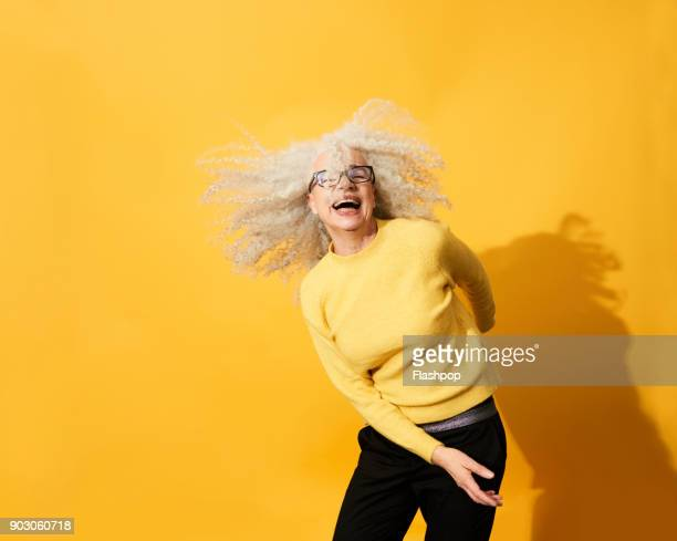 portrait of mature woman dancing, smiling and having fun - yellow stock pictures, royalty-free photos & images