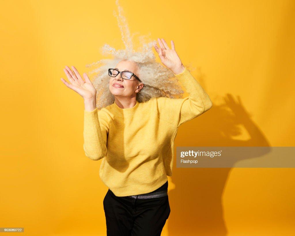 Portrait of mature woman dancing, smiling and having fun : Stock-Foto