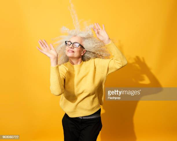 portrait of mature woman dancing, smiling and having fun - graues haar stock-fotos und bilder
