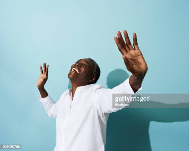 portrait of mature woman dancing, smiling and having fun - empowered woman stock photos and pictures