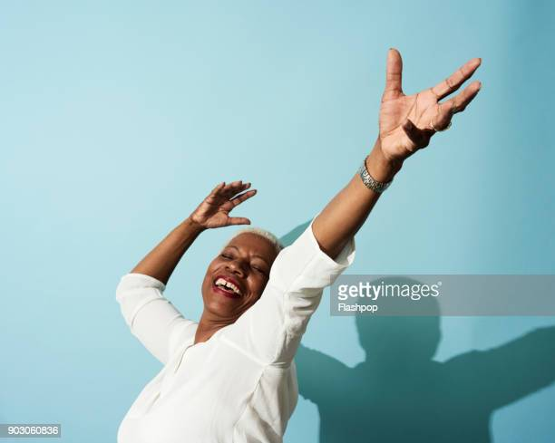 Portrait of mature woman dancing, smiling and having fun