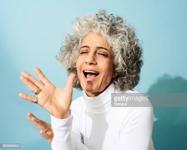 portrait of mature woman dancing, smiling and having fun - woman blue background stock pictures, royalty-free photos & images