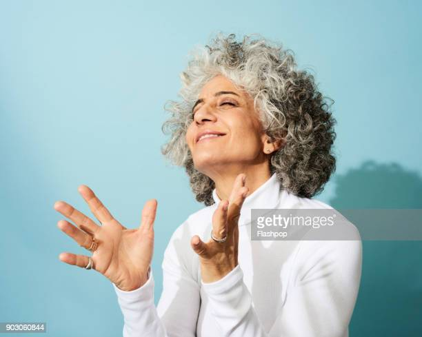 portrait of mature woman dancing, smiling and having fun - blue background stock pictures, royalty-free photos & images