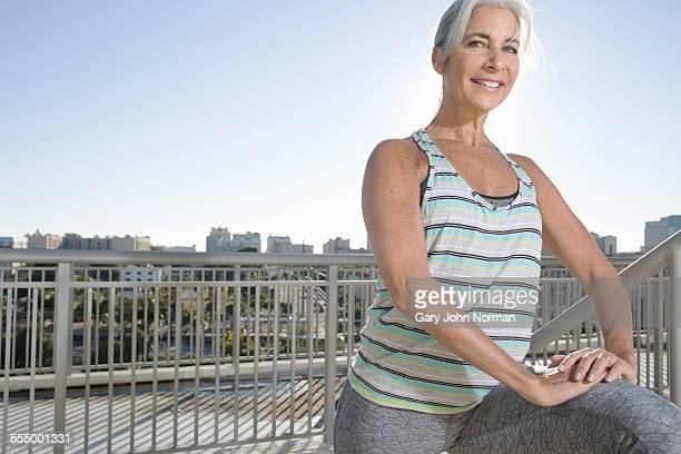 Portrait of mature woman doing warm up exercises on city balcony