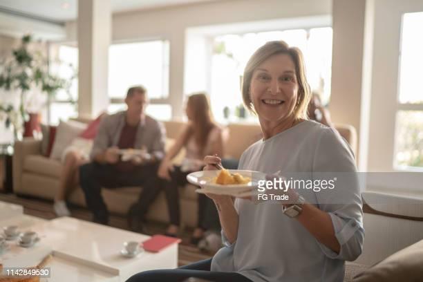 portrait de femme mature mangeant le gâteau au temps de famille de café - groupe moyen de personnes photos et images de collection