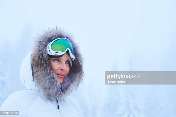 portrait of mature woman gazing at falling snow, gstaad, switzerland - gstaad stock pictures, royalty-free photos & images