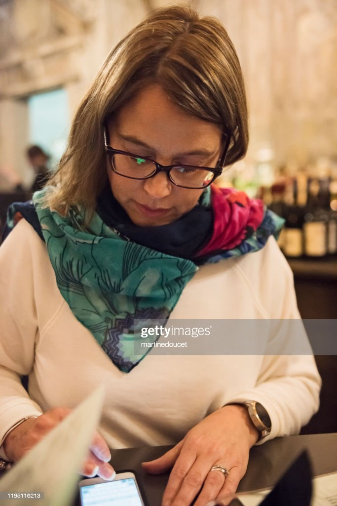 Portrait of mature woman having a drink in bar. : Stock Photo