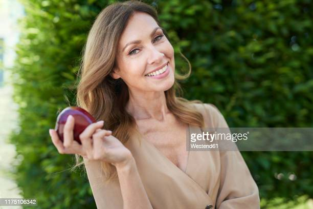 portrait of mature woman holding an apple, hedge in the background - apple fruit stock pictures, royalty-free photos & images