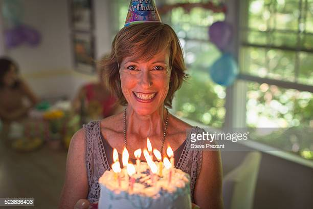 Portrait of mature woman holding birthday cake with candles