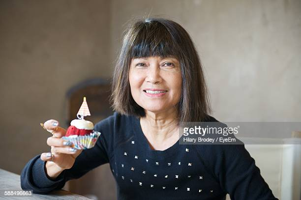 Portrait Of Mature Woman Holding Cupcake At Home