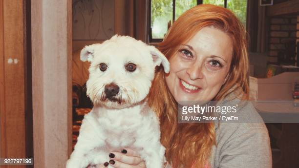 Portrait Of Mature Woman Holding Dog At Home