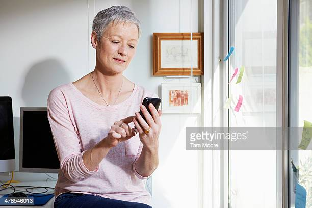 portrait of mature woman holding mobile in office