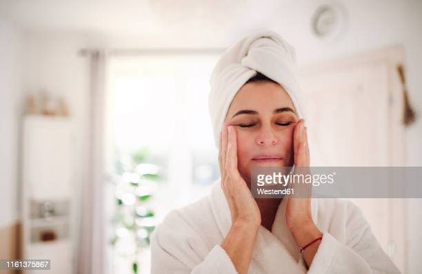 portrait of mature woman in a bathroom at home applying moisturizer - skin care stock pictures, royalty-free photos & images