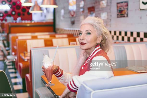 portrait of mature woman in baseball jacket with milkshake in 1950s diner - young at heart stock pictures, royalty-free photos & images