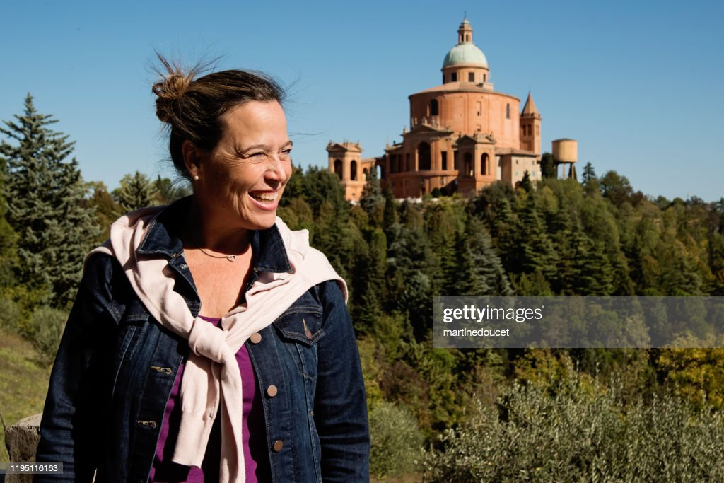 Portrait of mature woman in front of the Santuary of the Madonna di Santa Luca. : Stock Photo