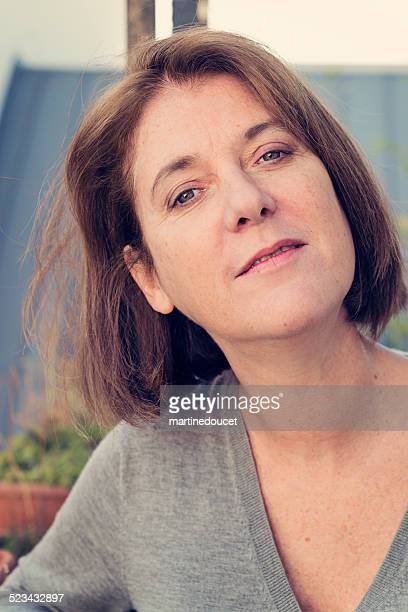 Portrait of mature woman in her fifties outdoors on balcony.