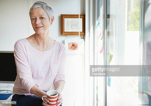 portrait of mature woman in home office - adults only stock pictures, royalty-free photos & images